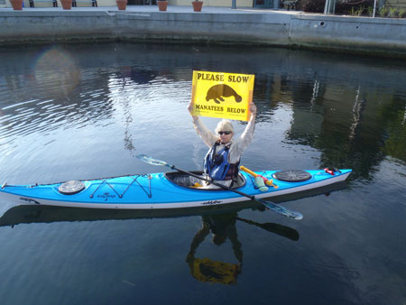 Tracy Colson with one of the Club's boating banners aboard her kayak on Kings Bay in Crystal River, Florida. (Photo by Steve Sapienza.)